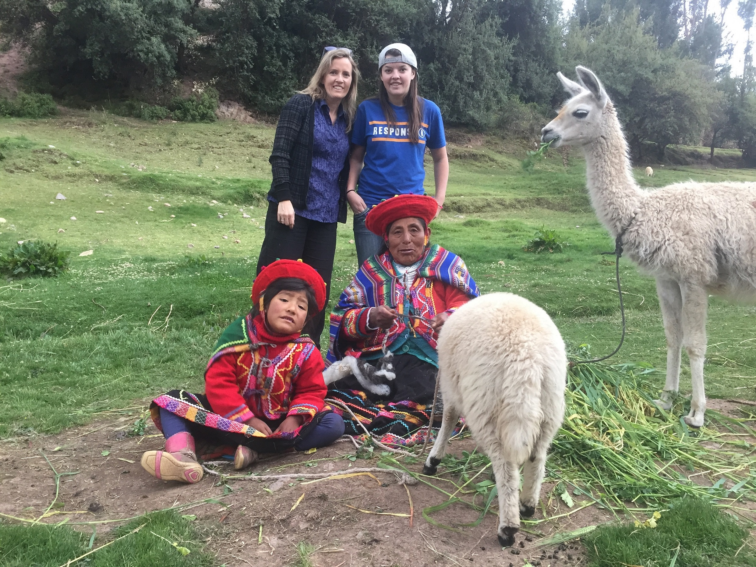 Cusco-city-tour-posing-with-Grandma-and-child-and-Llamas