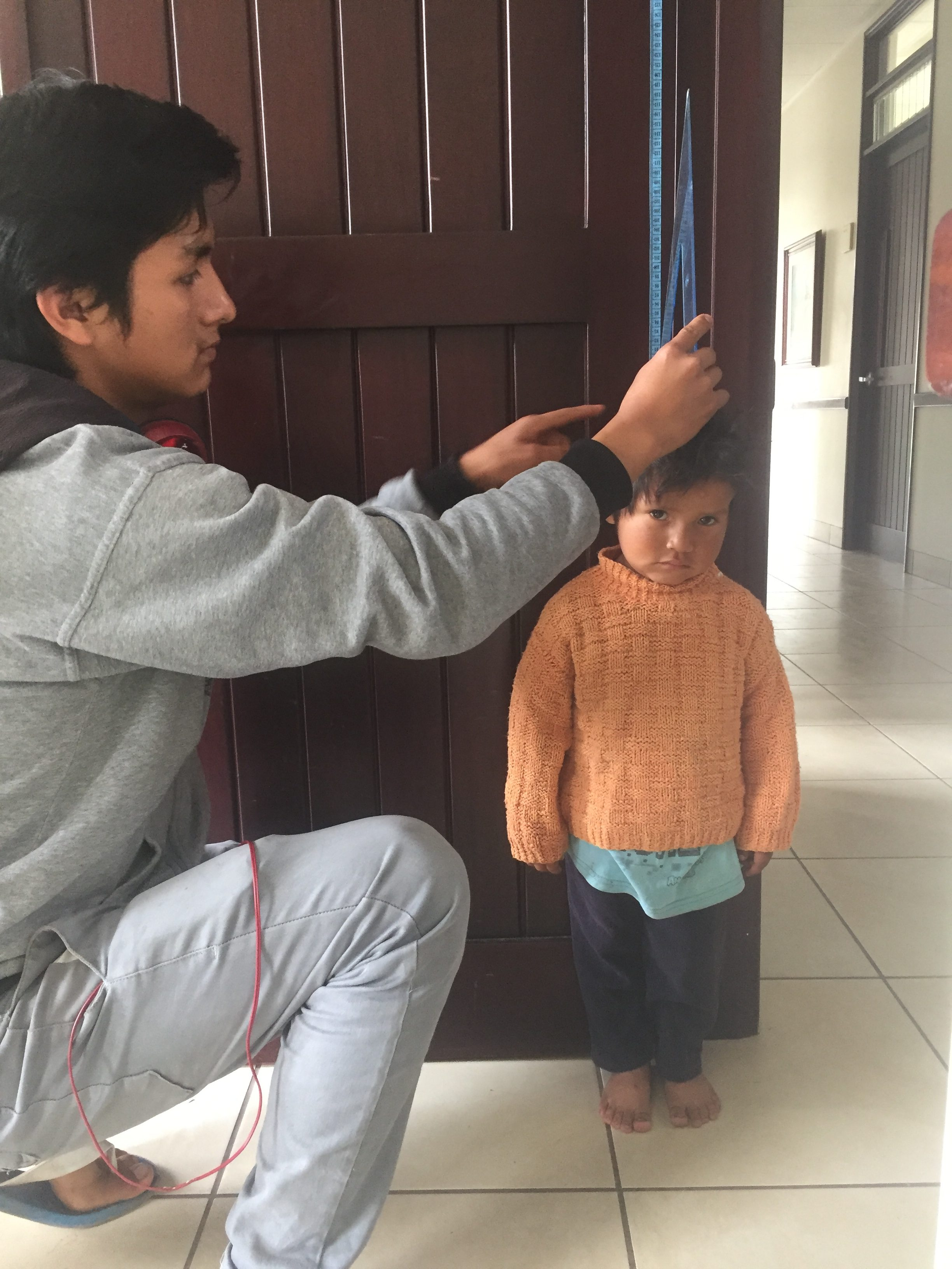Urubamba-screening-young-man-preparing-for-a-mission-measures-a-boy